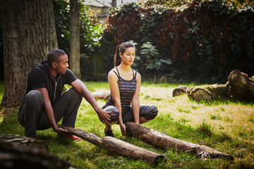Woman with personal trainer crouching to lift tree trunk in park