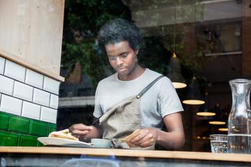 Waiter preparing order at cafe window