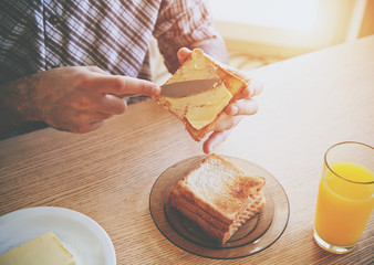 male hands spreading butter on toasted bread while morning break