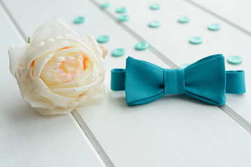 White rose, button and tie on a white wooden background