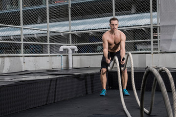 Man battle rope training at rooftop gym in Bangkok