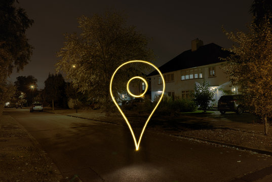 Light painted drop pin symbol floating on suburban street at night
