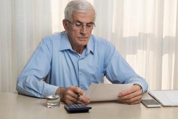 Serious senior man calculating home finances at home