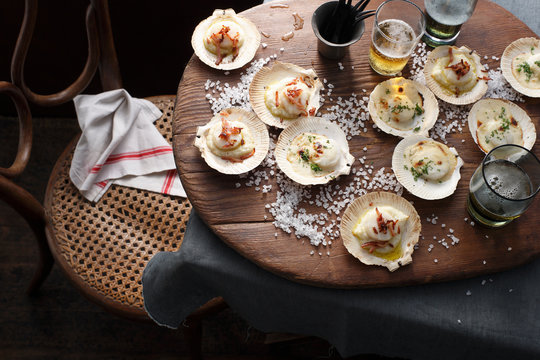 Scallops in shells on table