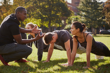 Personal trainer instructing man and women doing push ups in park