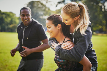 Personal trainer encouraging two women piggy backing in park