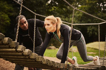 Personal trainer instructing young woman crawling on playground equipment in park