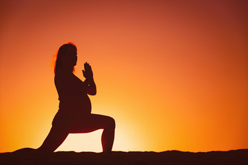 Silhouette of pregnant woman doing yoga on beach