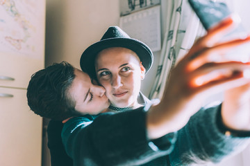 Young lesbian couple taking smartphone selfie in kitchen