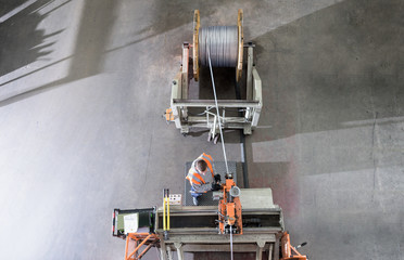 Worker winding electrical cables at cable storage facility, overhead view