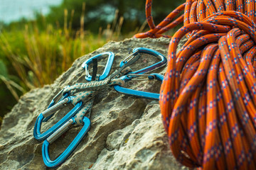 Safety harness with quick-draws and climbing equipment outdoor on a rock.