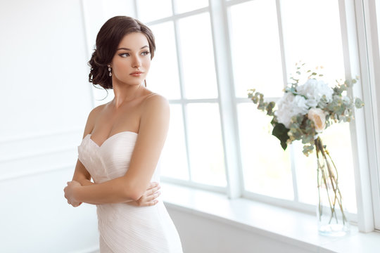 Stunning young bride near window at home