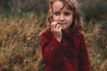 Portrait of girl chewing long grass in field