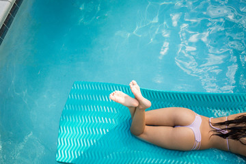 High angle neck down view of young woman sunbathing in swimming pool, Santa Rosa Beach, Florida, USA