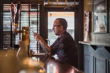 Barman sitting at bar counter with smartphone