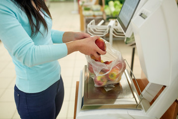 woman weighing apples on scale at grocery store