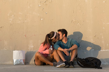 Couple kissing in front of concrete wall