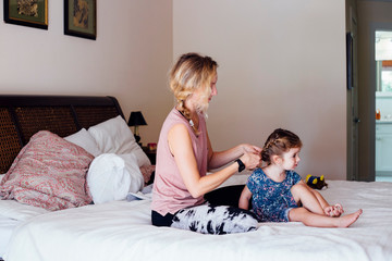 Woman sitting on bed plaiting toddler daughter's hair
