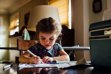 Female toddler at table colouring in colouring book