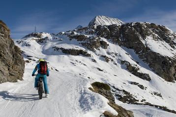 Sciatore con ebike - mountain bike elettrica - fat bike da neve, che sale in alta montagna con gli sci caricati sulla bici, Riale, Val Formazza, Ossola, Alpi Italia