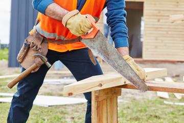 Zimmermann sägt Holz mit dem Fuchsschwanz