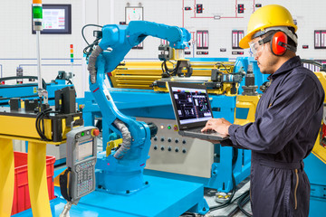 Engineer using laptop computer for control automatic robotic arm