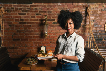 Woman holding plates of burger and french fries