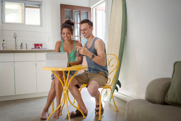 Young couple at kitchen table using laptop