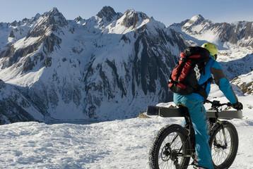 """ebike, mountain bike elettrica o """"fat bike"""" da neve, con ruote larghe, alta montagna, con gli sci caricati sulla bicicletta per fare sci alpinismo, inverno, Valle Formazza, Ossola, Alpi, Italia"""