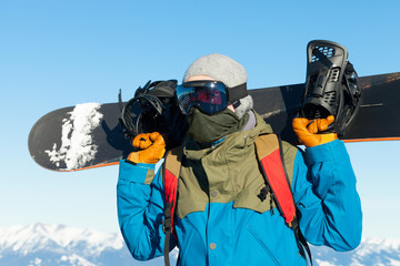 Male snowboarder holding board behind his sholders at the very top of a mountain