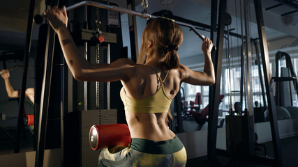 Brunette in a gym flexing back muscles on aquipment.