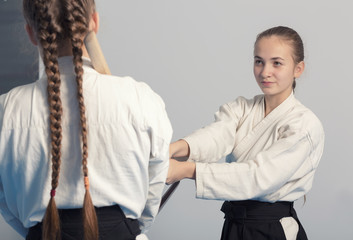 Two girls practice sword on Aikido training on white background. Selective focus