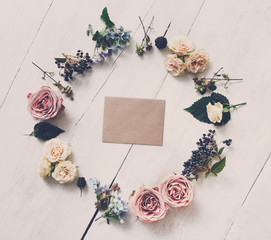 Empty greeting card and flowers circle on white wood