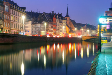 Picturesque quay and church of Saint Nicolas with mirror reflections in the river Ile during morning blue hour, Strasbourg, Alsace, France