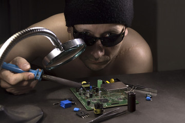A man in a black hat and sunglasses with a soldering iron mounts radio-electronic circuits at the table.