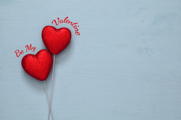 Couple of red glitter hearts on wooden background