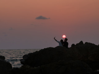 Silhouette lover shooting selfie photo at the sea when sunset cl