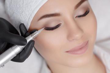 Cosmetologist making permanent make up at beauty salon