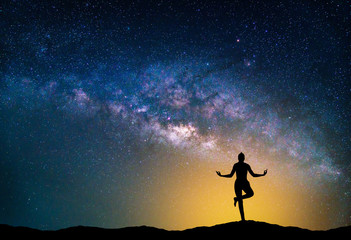 Wall Mural - Landscape with Milky way galaxy. Night sky with stars and silhouette woman practicing yoga on the mountain.