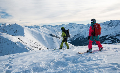 Two snowboarders on the mountain top just before riding down the slope