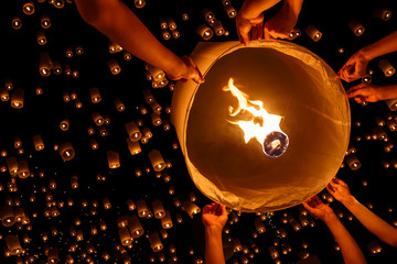 A floating lantern being set free amongst many others at night.