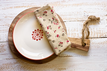 Off-white empty plate with red board on round cutting board, linen floral napkin, white plank wood background, Provence style, rural kitchen interior, minimalistic, kinfolk,flat lay