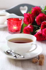 Romantic morning Tea for two with candles and bouquet of roses