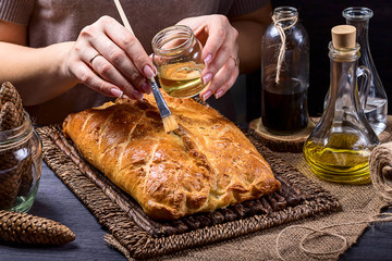 Pie greased with olive oil on a brown background