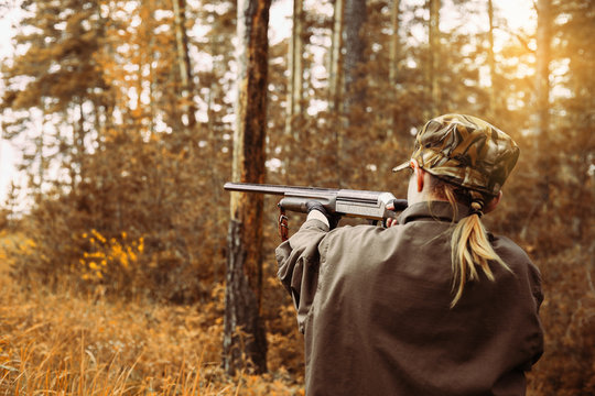 Autumn hunting season. Woman hunter with a gun.