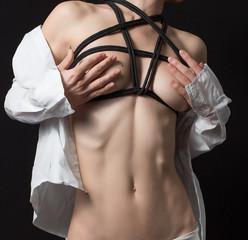 Nude woman in shirt with shibari in studio