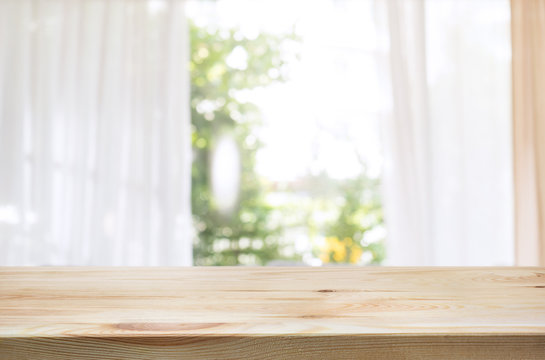 Wood table top on blur of curtain window and abstract green from garden background