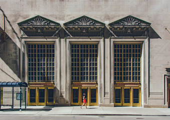 Woman walking beside a building in Chicago, Illinois.