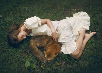 A girl lying on the ground with a fox outdoors.