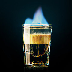 A shot of liquor burning with a blue flame.